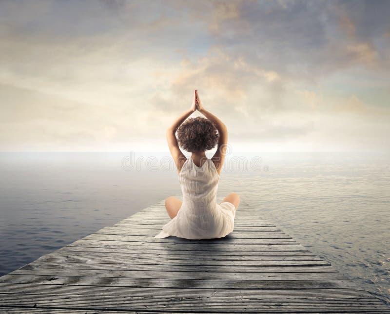 Женщина ослабляя делающ йогу стоковая фотография rf