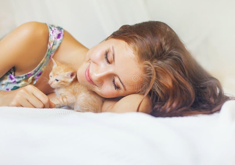 Женщина ослабляя на кровати с очень милым котенком стоковое изображение rf