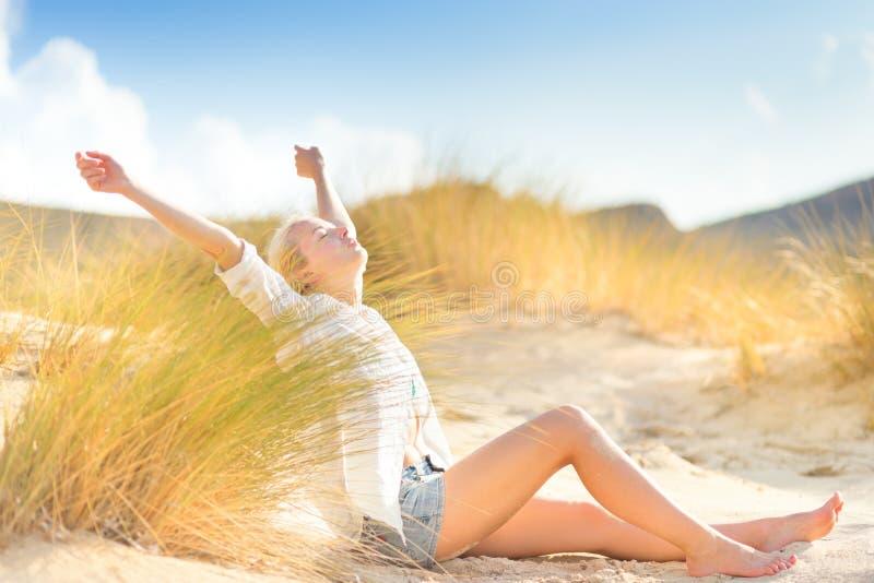Женщина ослабляя на песчанных дюнах стоковые фото