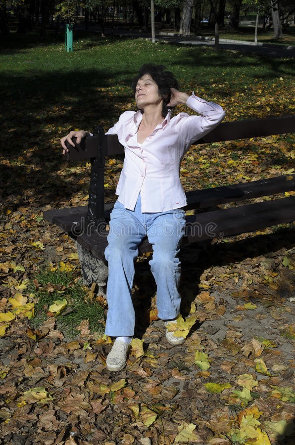 Женщина ослабляя на стенде в осени стоковое изображение rf