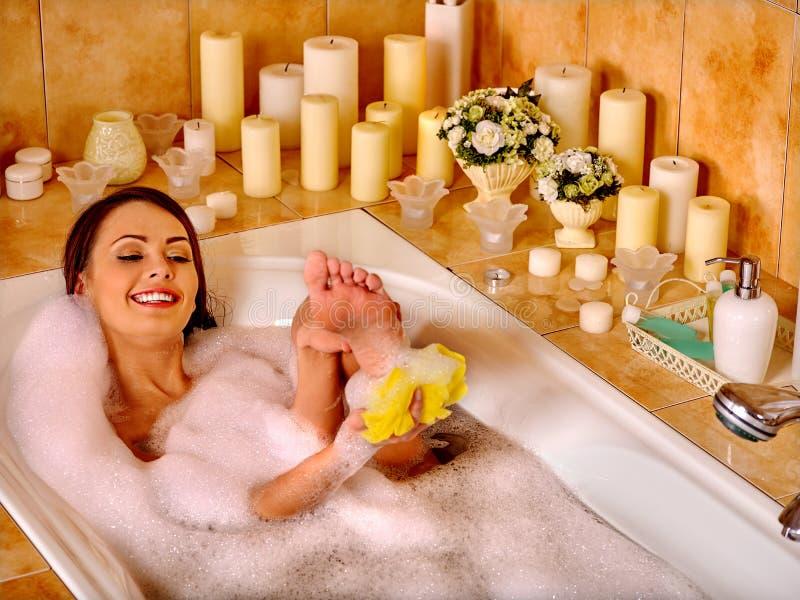 Женщина ослабляя дома ванну стоковое фото