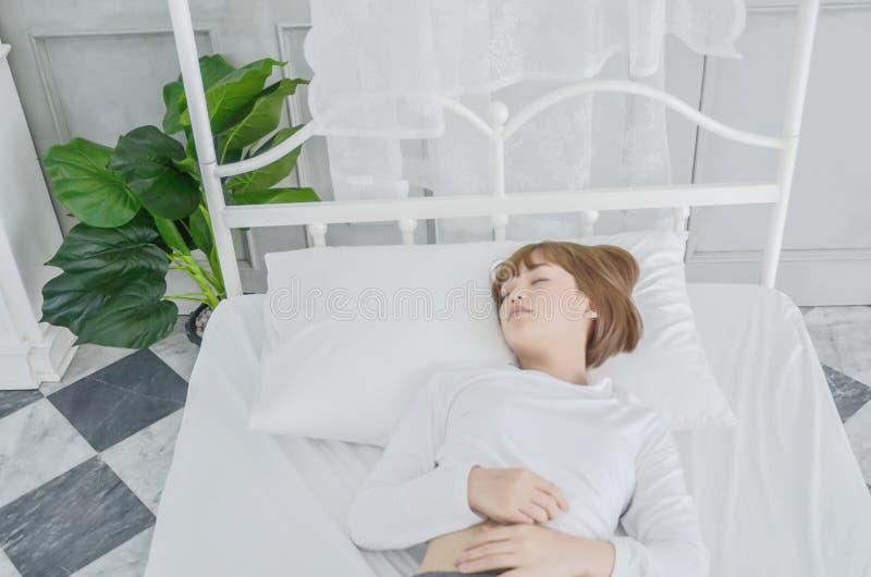 Женщина отдыхала на кровати в ее спальне в утре стоковое фото rf