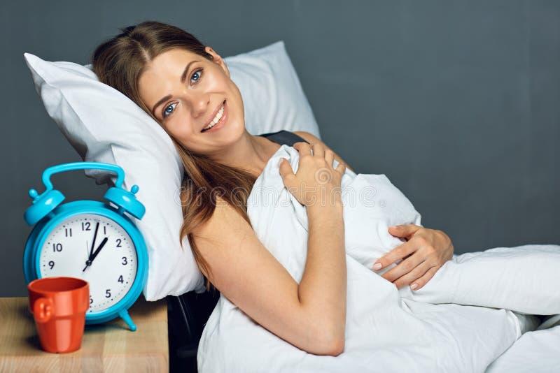 Женщина отдыхая в месте службы офиса с большим будильником стоковое изображение rf