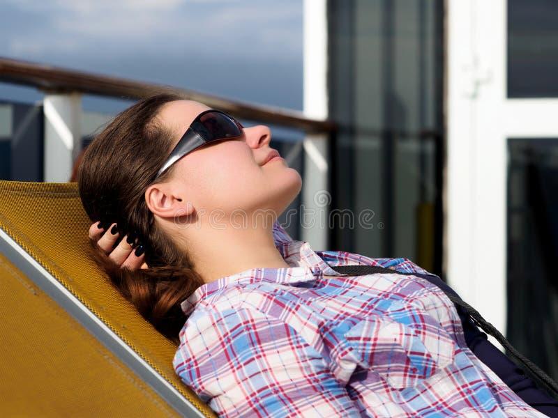 Женщина отдыхая на lounger стоковое фото rf