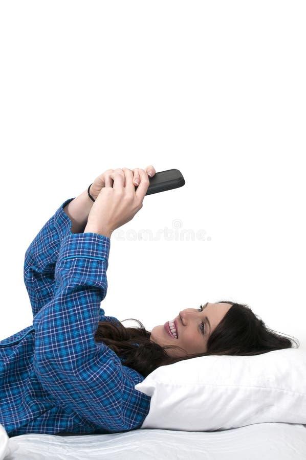 Женщина отправляя СМС в кровати стоковая фотография rf