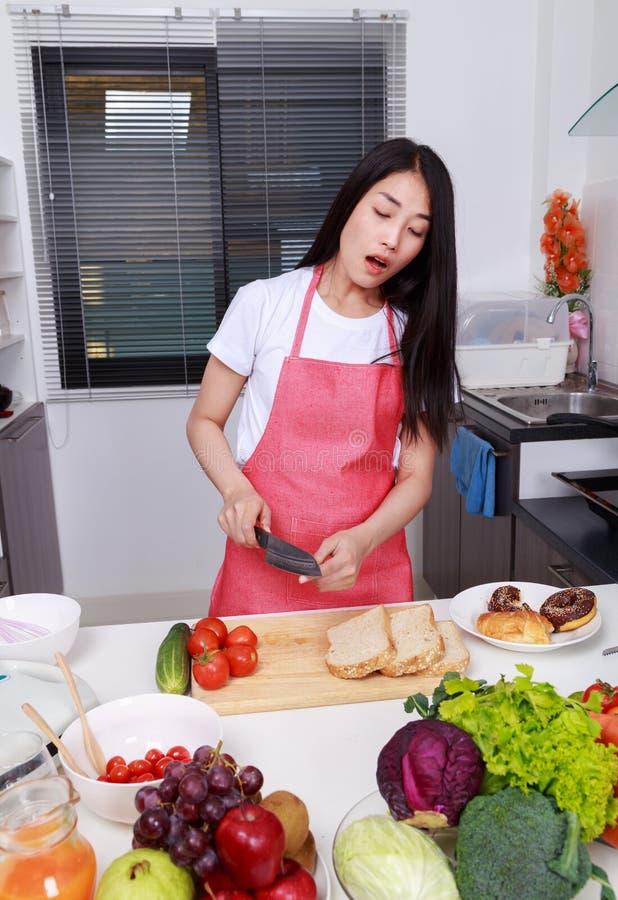 Женщина отрезала ее палец пока варящ в комнате кухни стоковые изображения rf