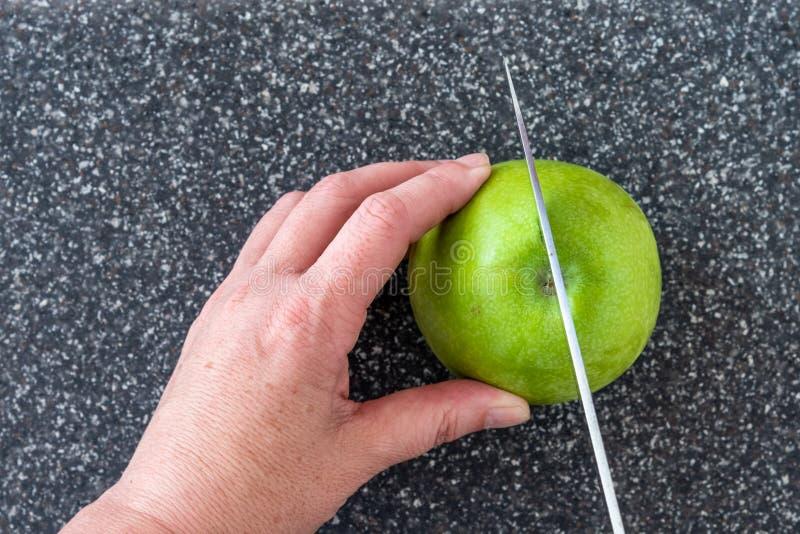 Женщина отрезая зеленое яблоко Смита бабушки на пластиковом человеке сделала faux серые разделочную доску гранита, руки и нож шеф стоковое изображение rf