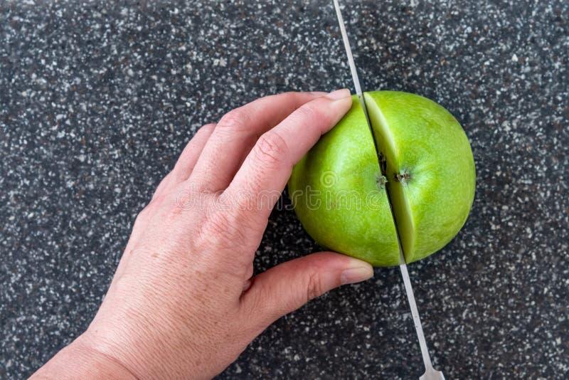 Женщина отрезая зеленое яблоко Смита бабушки на пластиковом человеке сделала faux серые разделочную доску гранита, руки и нож шеф стоковые фото