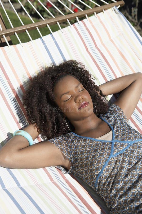Женщина отдыхая на гамаке стоковые фотографии rf