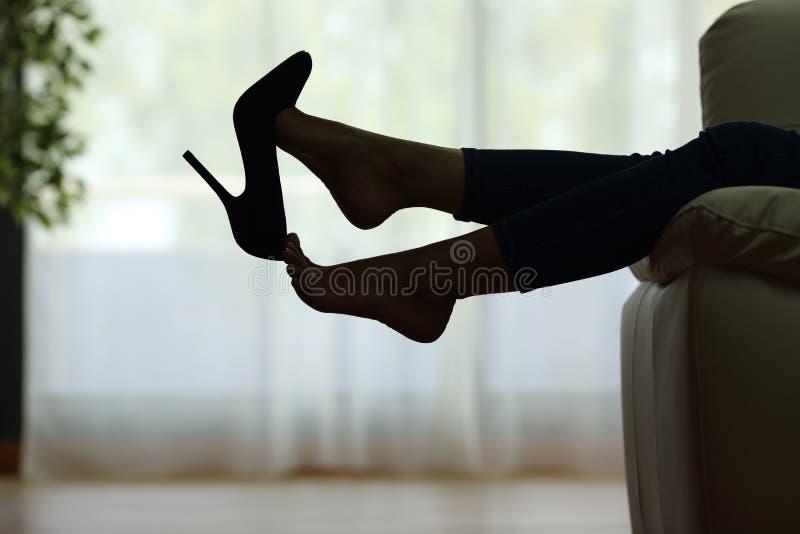 Женщина отдыхая при ноги принимая ботинки стоковая фотография