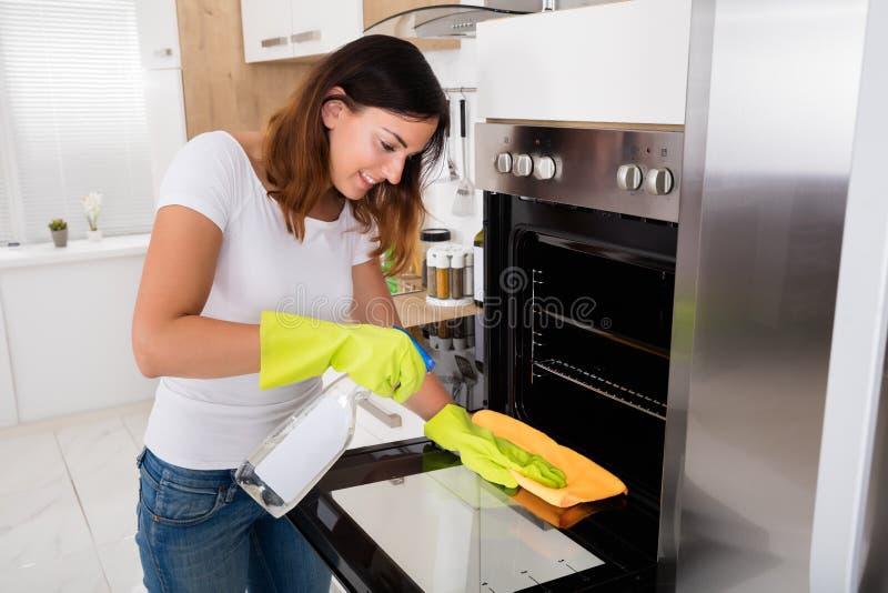 Женщина очищая печь в кухне стоковые изображения