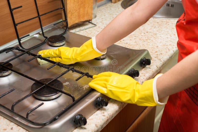 Женщина очищая плиту в кухне Концепция домоустройства стоковое фото