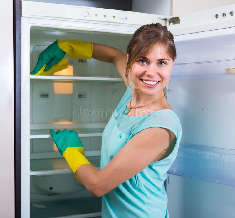 Женщина очищая пустой холодильник стоковое фото