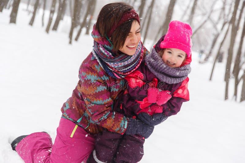 Женщина, дочь сидя на снеге стоковая фотография