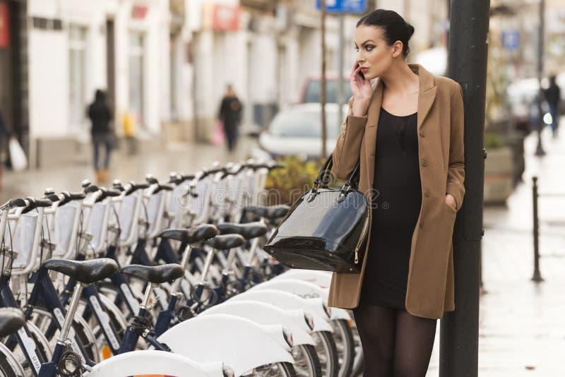 Женщина одетая зимой около велосипеда стоковая фотография rf