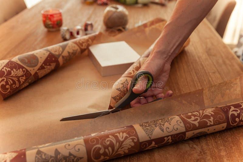 Женщина пакует подарки в упаковочную бумагу для праздников как день рождения, рождество, valentyn, Новый Год, свадьба стоковые изображения rf
