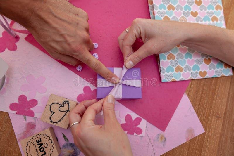 Женщина пакует подарки в упаковочную бумагу для праздников как день рождения, рождество, valentyn, Новый Год, свадьба стоковая фотография