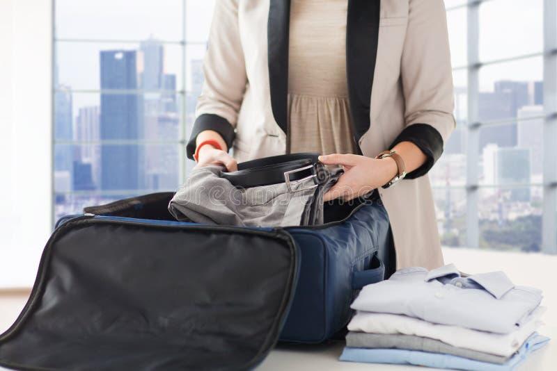Женщина пакуя официально мужские одежды в перемещение кладет в мешки стоковые фотографии rf