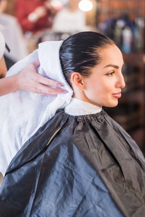 Женщина парикмахера обтирает ее волосы клиентов с полотенцем стоковая фотография rf