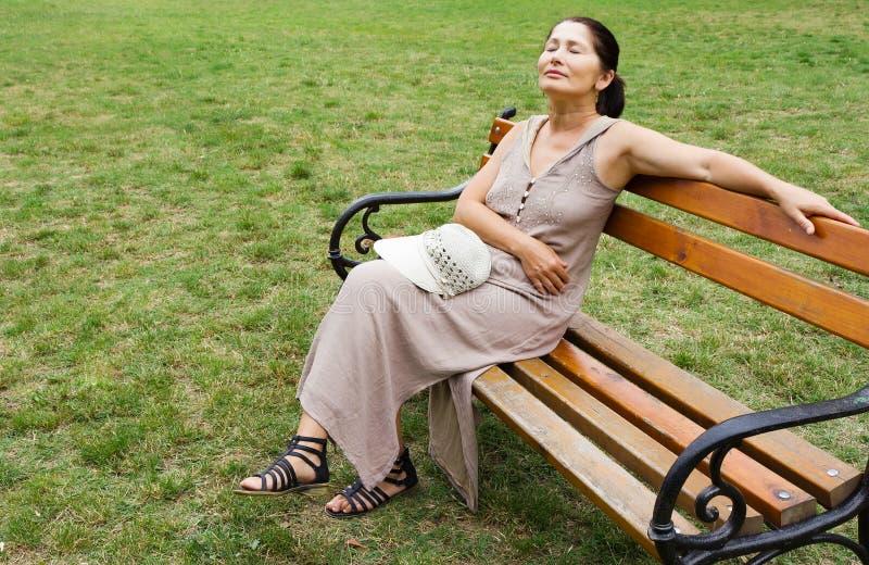 женщина парка стенда сидя стоковое изображение