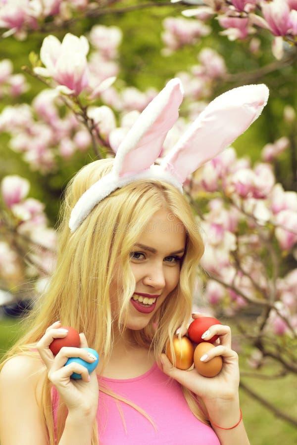 Женщина пасхи с яйцами в ушах зайчика на магнолии, весне стоковая фотография rf