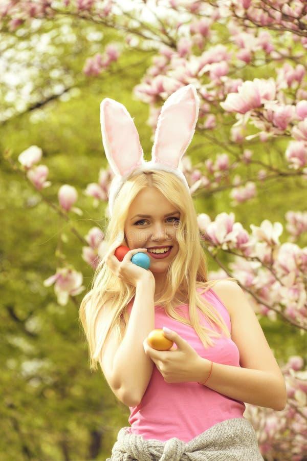 Женщина пасхи с яйцами в ушах зайчика на магнолии, весне стоковые фотографии rf