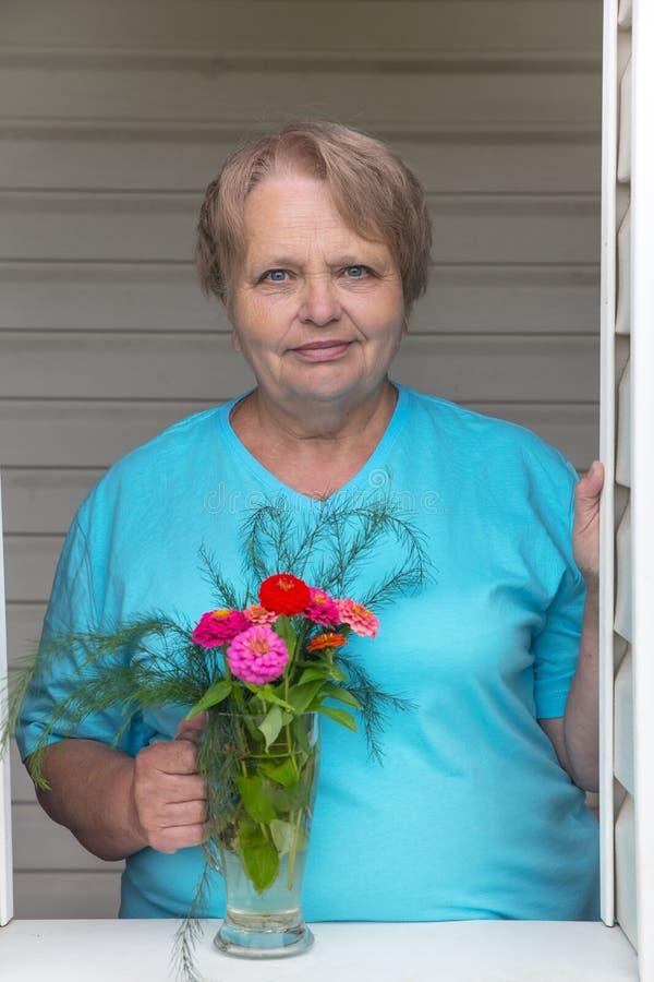 Женщина пенсионера на окне с пуком цветков стоковое изображение