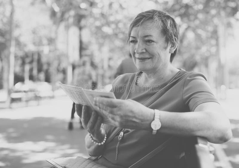 Женщина пенсионера читая outdoors стоковые фотографии rf