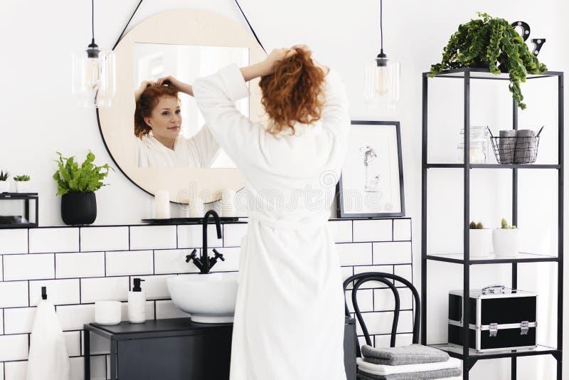 Женщина перед зеркалом в минимальном интерьере ванной комнаты с плакатом, стулом и заводами Реальное фото стоковое фото rf