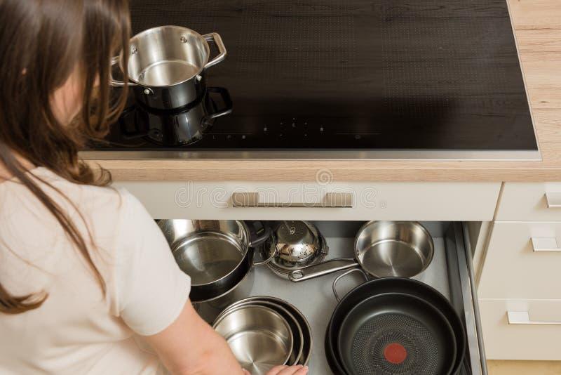 Женщина перед современным плитаом с открытым ящиком под плитой стоковые фотографии rf