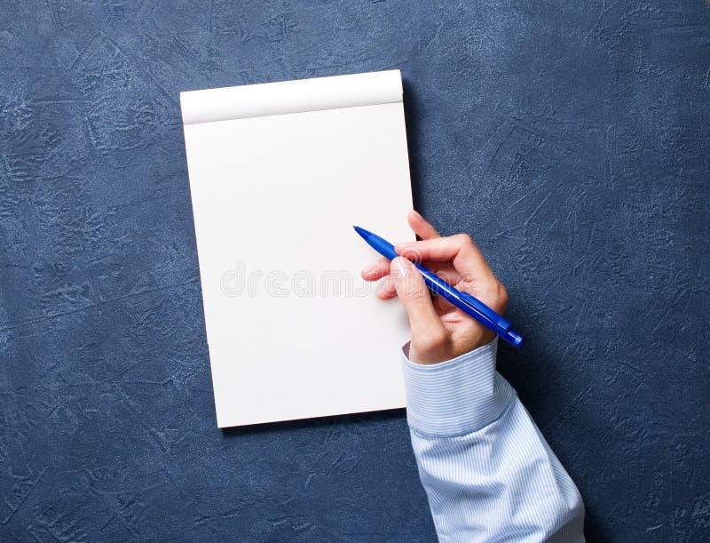женщина пишет в тетради на синей таблице, руке в рубашке держа карандаш, чертеж sketchbook, взгляд сверху стоковое изображение