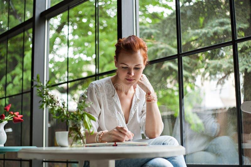 Женщина пишет в тетради стоковое изображение