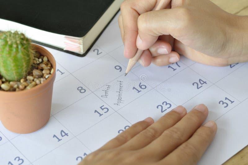 Женщина пишет назначение дантиста в плановике календаря стоковое фото rf