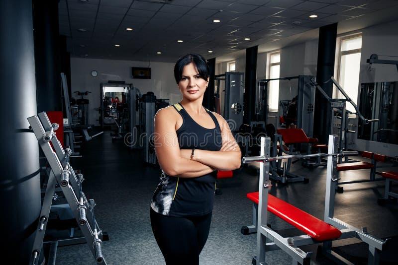 Женщина плюс размер в спортзале представляя счастливый, женский вес XXL проигрышный, f стоковое изображение rf