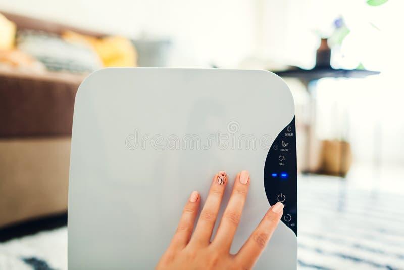 Женщина поворачивает dehumidifier на использовать сенсорную панель дома Современный прибор airdryer для воздуха чистки стоковое фото rf