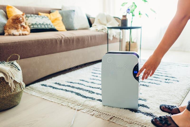Женщина поворачивает dehumidifier на использовать сенсорную панель дома Современный прибор airdryer для воздуха чистки стоковые изображения rf