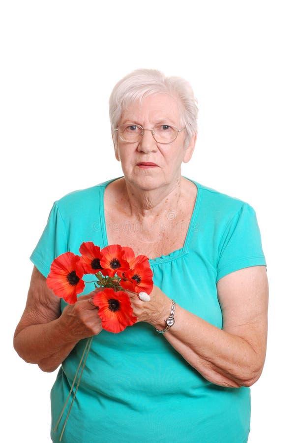 женщина поддельных маков удерживания красная старшая стоковое фото rf