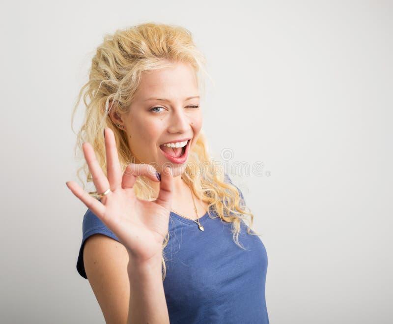 Женщина подмигивая и показывая одобренному знаку стоковое изображение