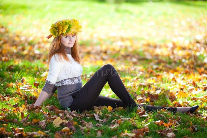 Женщина подростка в венке кленовых листов лежа o стоковое изображение rf
