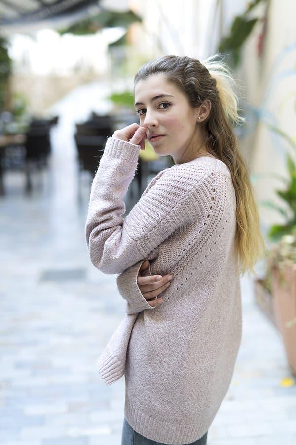Женщина подростка с рукой на ее стороне смотря камеру стоковые фотографии rf
