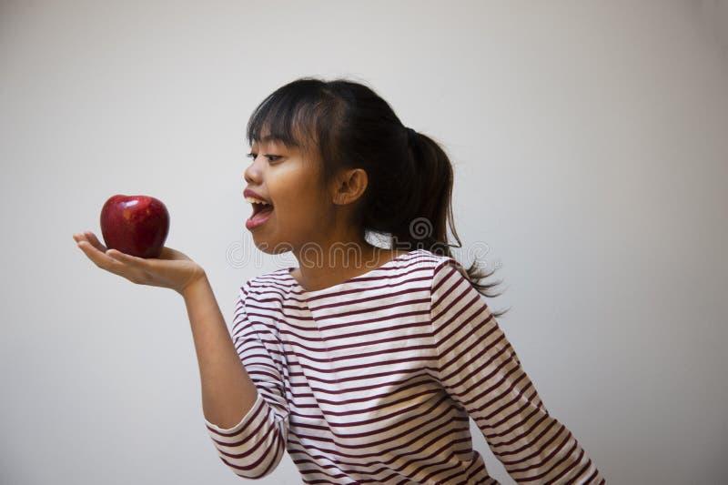 женщина подростка 20s филиппинская с красным портретом яблока на случайной предпосылке ткани стоковое изображение rf