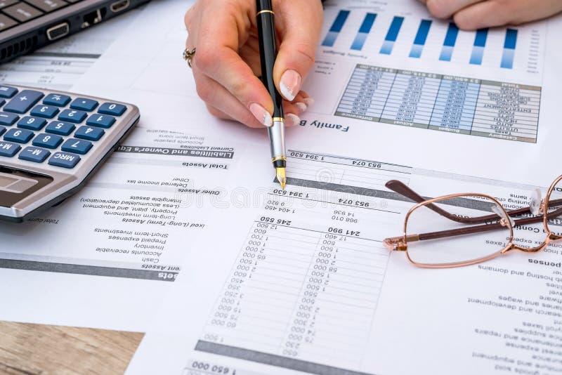 Женщина подсчитывая финансовые данные анализируя с калькулятором стоковые фотографии rf