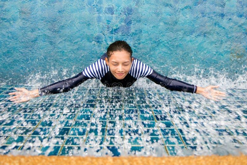 Женщина под ливнем в бассейне стоковое фото
