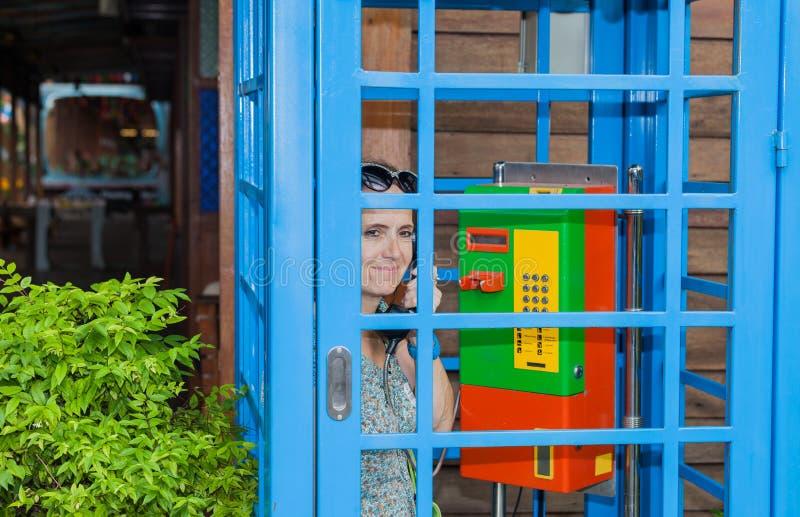 Женщина позвоненная по телефону в красочной телефонной будке стоковое фото
