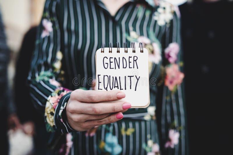 Женщина показывает блокнот с равенством полов текста стоковое изображение rf