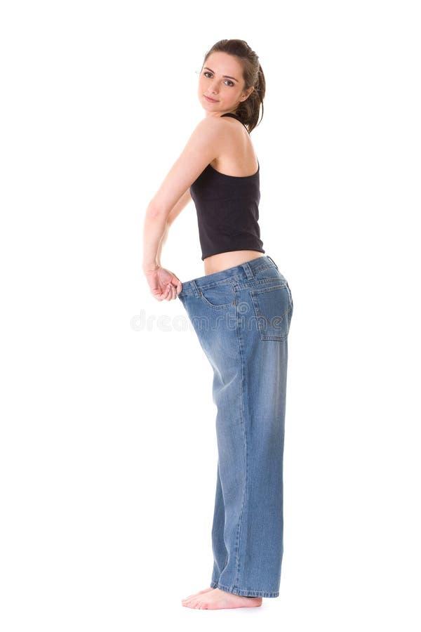 Женщина показывает ей старые огромные джинсыы, потерю wieght стоковые изображения rf