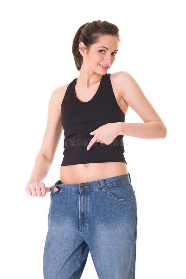 Женщина показывает ей старые огромные джинсыы, потерю wieght стоковые фотографии rf
