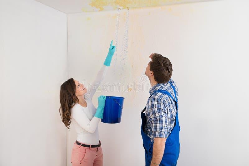 Женщина показывая воду протекая от потолка к обслуживанию Гаю стоковые фотографии rf
