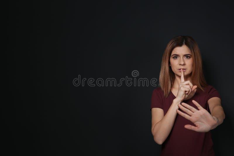 Женщина показывая жест HUSH в языке жестов на черной предпосылке стоковая фотография rf