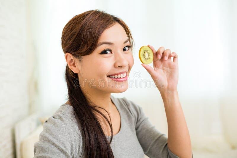 Женщина показывая куски плодоовощ кивиа стоковое изображение rf